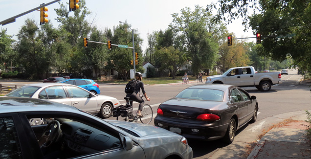 A bicycle commuter rides among motor vehicle traffic