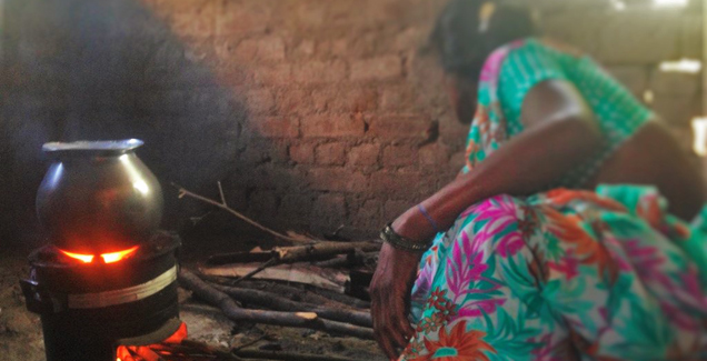 A woman in India cooking a meal on a traditional style wood stove.