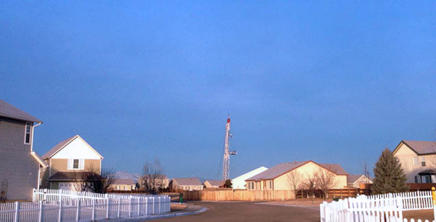 A neighborhood with a fracking rotator in the background