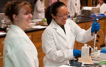 Microbiology undergraduate students pipetting in laboratory class